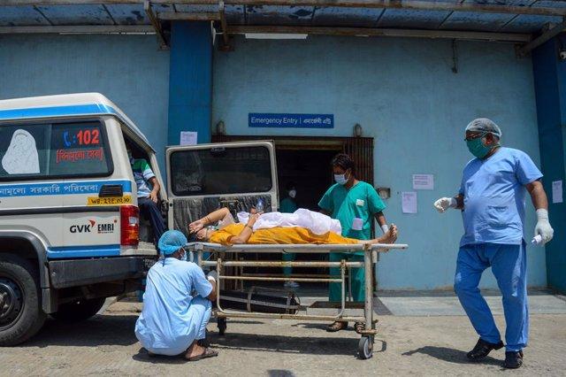 23 April 2021, India, Kolkata: Medics transport a patient suffering from coronavirus complications into a critical care unit at a Kolkata hospital. Photo: Debarchan Chatterjee/ZUMA Wire/dpa