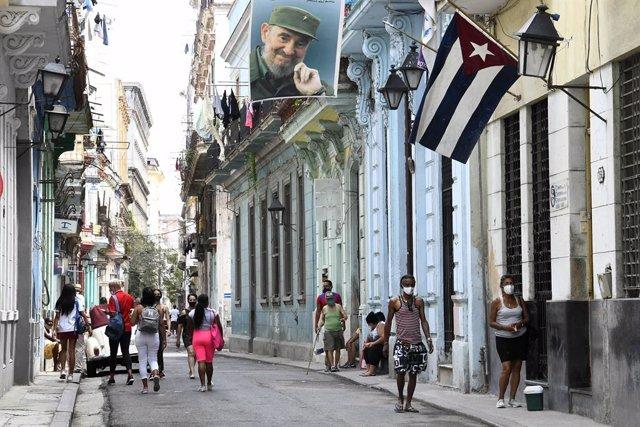 Personas con mascarilla pasean por una calle de La Habana