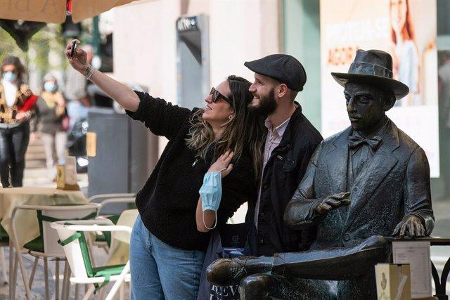 Una pareja posa junto a la estatua del poeta Fernando Pessoa, en el centro de Lisboa.