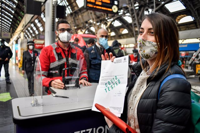 "16 April 2021, Italy, Milan: A young woman shows the result of her Corona test at a platform counter in a train station in Milan. Italy's railway company Trenitalia offers so-called ""covid-free"" connections between Rome and Milan, only for travellers with"
