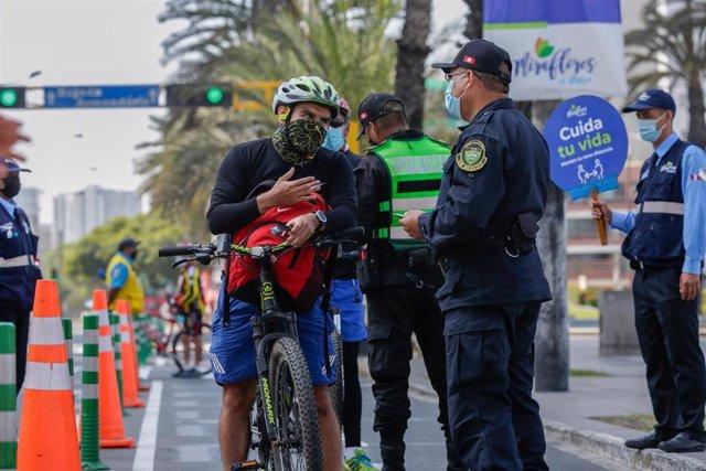 Un ciclista es sometido a un control policial en Lima, Perú, en el marco de las restricciones impuestas por el coronavirus.
