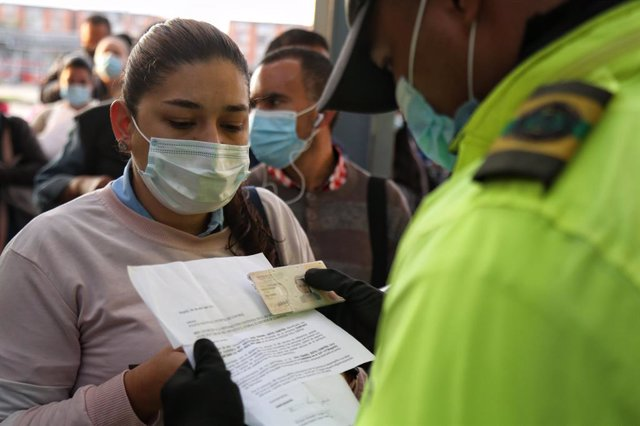 23 April 2021, Colombia, Bogota: A policeman checks the documents and permits of a woman wearing a mask to allow her access to public transport during the first day of the third quarantine. Photo: Camila Díaz/colprensa/dpa
