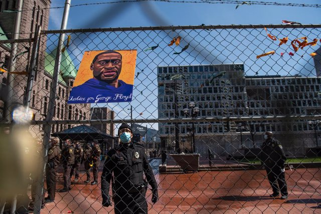 02 April 2021, US, Minneapolis: Police officers remove the photos and locks from the fencing outside the Hennepin County Courthouse, where the trial of a former Minneapolis police officer Derek Chauvin in the death of George Floyd take place. Protestors p