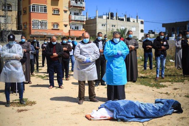 23 April 2021, Palestinian Territories, Deir al Balah: Palestinians perform a funeral ceremony for a woman who died of coronavirus in a cemetery in Deir Al-Balah city. Photo: Mahmoud Khattab/Quds Net News via ZUMA Wire/dpa