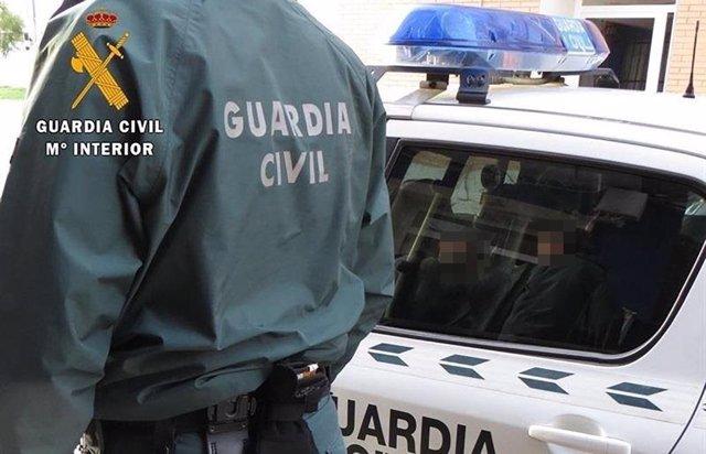Archivo - Un agente de la Guardia Civil junto a un coche patrulla.