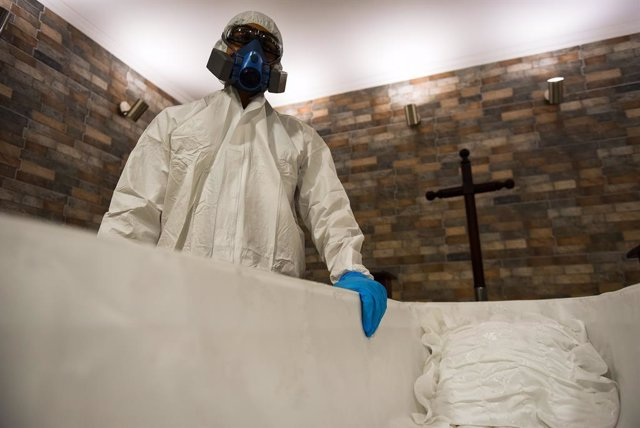 12 April 2021, Chile, Temuco: A staff member of the Lar de Cristo Funeral Home is seen dressed in full protective suit as he stands next to a casket. The funeral home reported a 20 percent increase in funeral services in the wake of the Coronavirus pandem