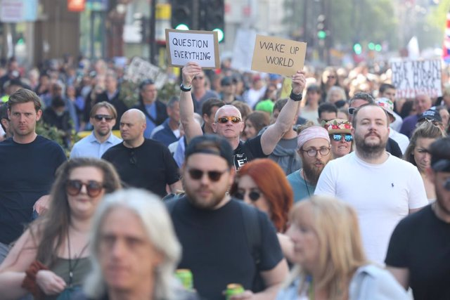 """24 April 2021, United Kingdom, London: A protester holds two placards reading """"Question everything"""" and """"Wake up world"""". Thousands marched on London's Oxford Street as part of the Unite For Freedom protest against the nationwide Corona restrictions. Prote"""