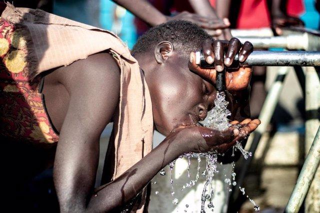 Una persona bebe agua de una fuente