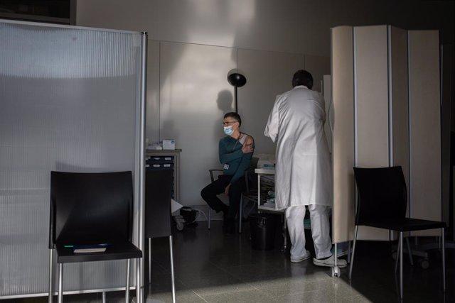 Archivo - Arxiu - Una infermera vacuna un professional sanitari amb la vacuna de Pfizer-BioNtech contra la covid-19 a l'Hospital de la Santa Creu i Sant Pau de Barcelona.
