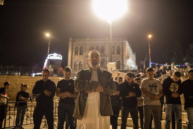 Musulmanes palestinos rezando junto a la Puerta de Damasco de la Ciudad Vieja de Jerusalén a la caída de la noche durante el Ramadán