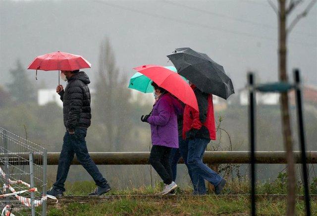 Archivo - Varias personas se refugian con un paraguas de la lluvia.