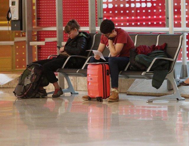 Archivo - Dos personas con su equipaje esperan su vuelo sentados en un banco en el Aeropuerto de Madrid-Barajas Adolfo Suárez, en Madrid a 21 de noviembre de 2019.