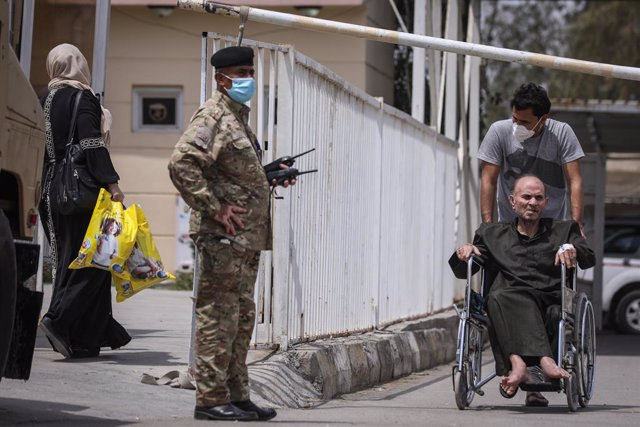 25 April 2021, Iraq, Baghdad: Amember of Iraqi Security forces stands guard outside Ibn al-Khatib Hospital, where a fire broke out early Sunday. According to the Iraqi Interior Ministry, 82 people died and some 110 others were injured in the early Sunday