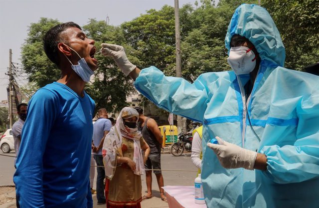15 April 2021, India, New Delhi: A healthcare worker in protective suit collects a mouth swab sample from a man for a COVID-19 RT-PCR test outside the DT City Centre Mall. Photo: Naveen Sharma/SOPA Images via ZUMA Wire/dpa