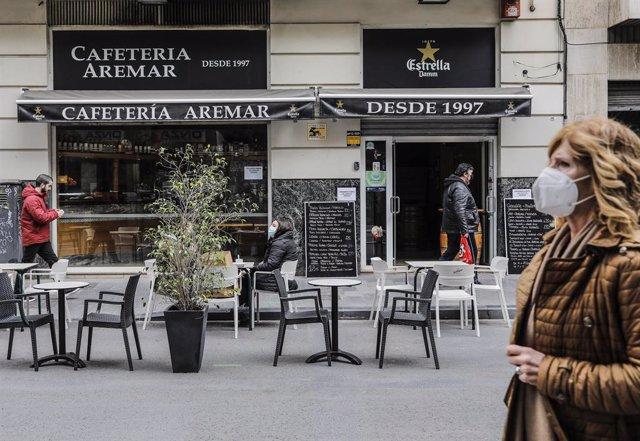 Archivo - Un mujer camina frente a una terraza el primer día de la apertura de la hostelería en Valencia