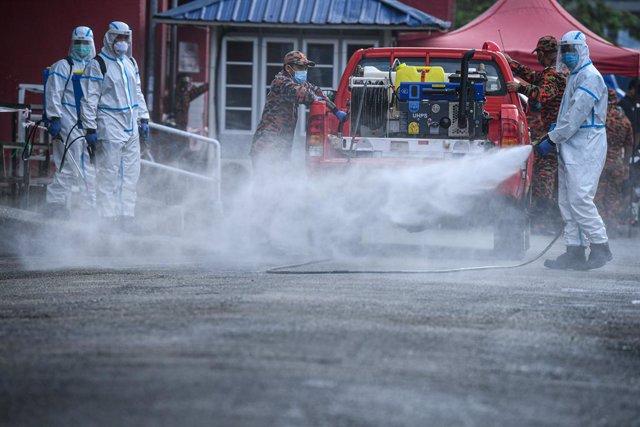 Archivo - Trabajadores desinfectando una calle en una ciudad de Malasia