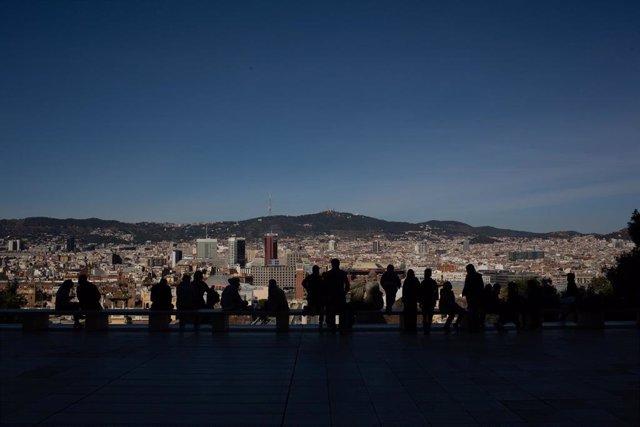 Archivo - Varias personas observan las vistas de Barcelona desde el Museo Nacional d'Art de Catalunya (MNAC), en Barcelona, Catalunya (España), a 11 de febrero de 2021