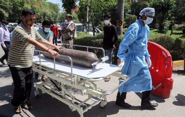 Trabajadores sanitarios entran con una bombona de oxígeno en un hospìtal de India en medio de la pandemia de coronavirus