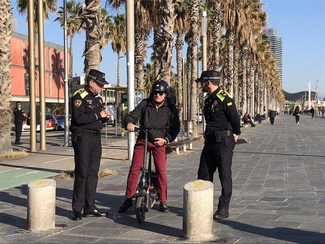 Archivo - Arxiu - Dos agents de la Guàrdia Urbana i un usuari del patinet elèctric a Barcelona.