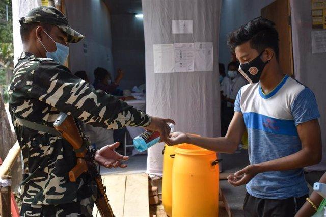 Un personal del Ejército de India suministra gel desinfectante a un joven.