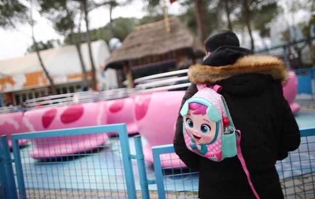 Archivo - Un hombre con una mochila en las inmediaciones de una atracción infantil del Parque de Atracciones.