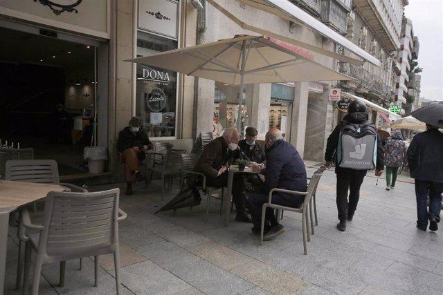 Varias personas en una terraza, el día en que entran en vigor nuevas medidas en la hostelería, en Vigo, Pontevedra, Galicia, (España). La Xunta ha decretado desde este viernes a las 00.00 el paso de la ciudad de Vigo a nivel medio debido a la crisis del C