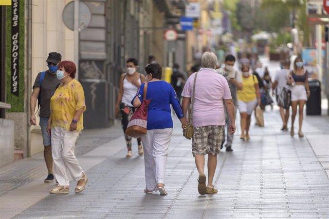 Archivo - Personas con mascarilla paseando por la calle.