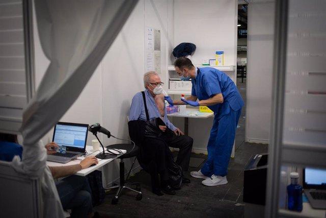 Una sanitaria vacuna a un hombre en el circuito de vacunación de Fira de Barcelona, a 26 de abril de 2021, en Barcelona, Cataluña (España). El circuito de vacunación es una prueba piloto de vacunación para futuras inoculaciones a gran escala cuando llegue