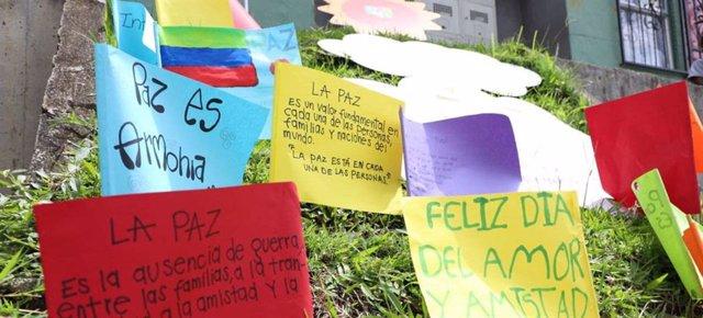 Archivo - Mensajes de paz escritos por niños cuelgan en un muro de las comunas de Medellín, en Colombia.