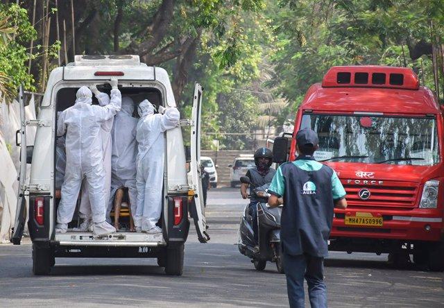 Trabajadores sanitarios trasladan a un paciente de coronavirus en la capital de India, Nueva Delhi