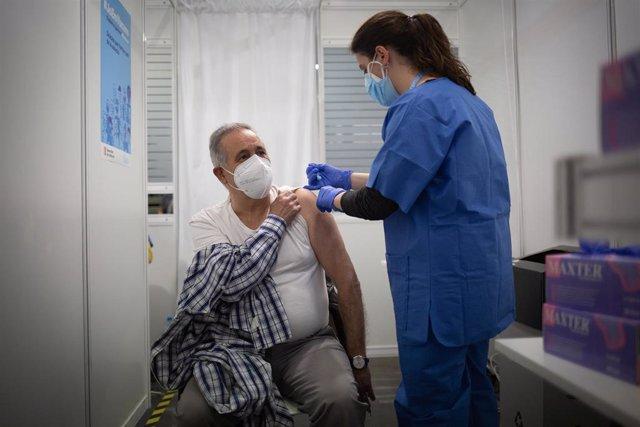 Una sanitaria vacuna a un hombre en el circuito de vacunación de Fira de Barcelona