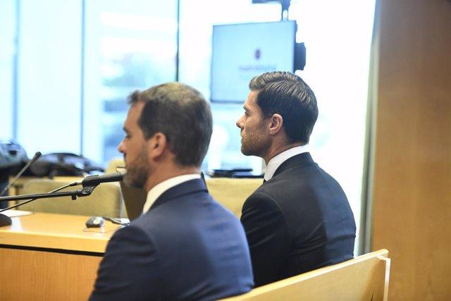 Archivo - El exfutbolista y entrenador Xabi Alonso (d) se sienta, junto al asesor fiscal Izan Zaldúa Azkuenaga (i), en el banquillo de los acusados de la Audiencia Provincial de Madrid para ser juzgado por tres delitos contra la Hacienda Pública durante l