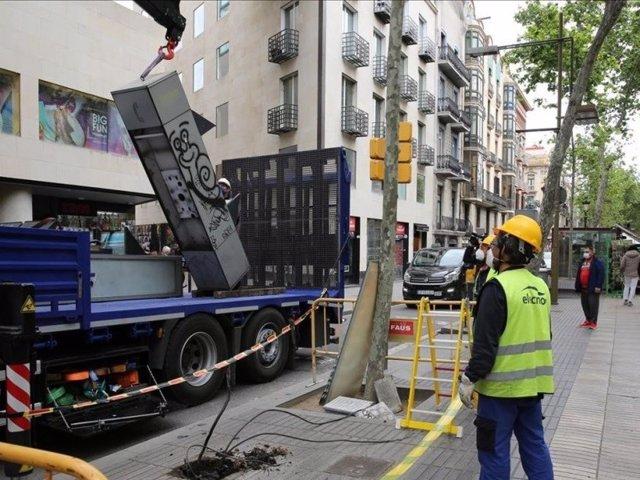 Operaris retiren les cabines telefòniques de la Rambla de Barcelona.