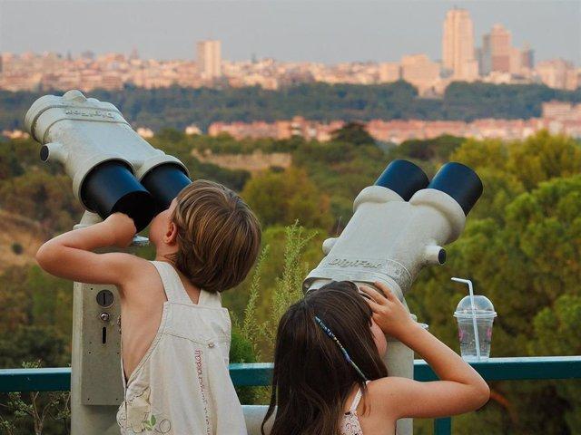 Archivo - Panorámica de la ciudad de Madrid vista por dos niños a través de unos binoculares