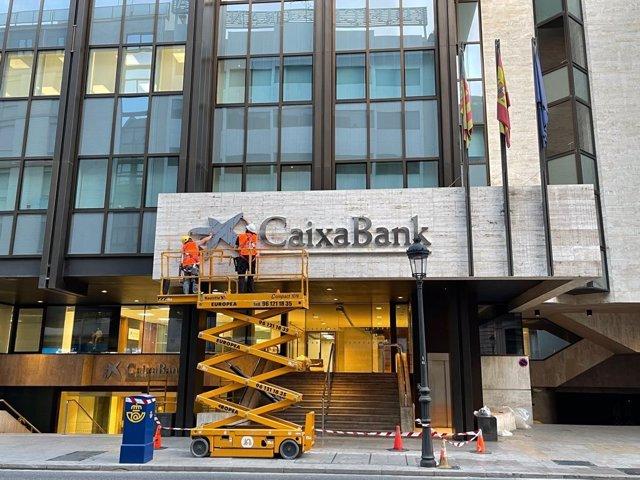 Archivo - Operarios colocan el logo de CaixaBank en el edificio que albergaba la sede de Bankia en València