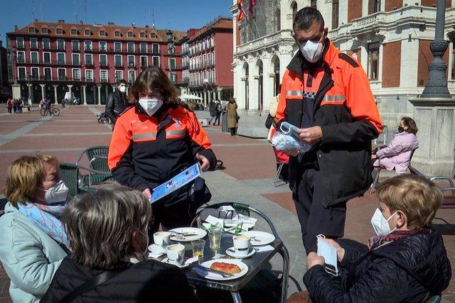 Voluntarios de Protección Civil informan sobre las medidas sanitarias a tres clientas de una terraza de Valladolid que cumplen correctamente la normativa.
