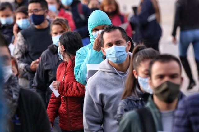 23 April 2021, Colombia, Bogota: People wearing masks queue in front of a checkpoint to access public transport on the first day of the third quarantine of April. Photo: Camila Díaz/colprensa/dpa