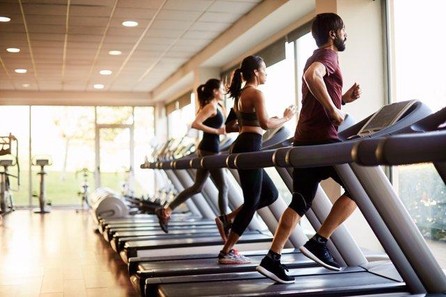 Archivo - Vista de una fila de cintas de correr en un gimnasio con gente.