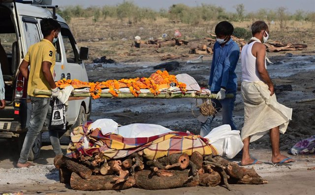 27 April 2021, India, Prayagraj: Family members and paramedics carry the bodies of victims who died who died of Covid-19 disease to the cremation sites at Phaphamau Ghat. India hit record numbers of Covid-19 infections worldwide for the sixth day running