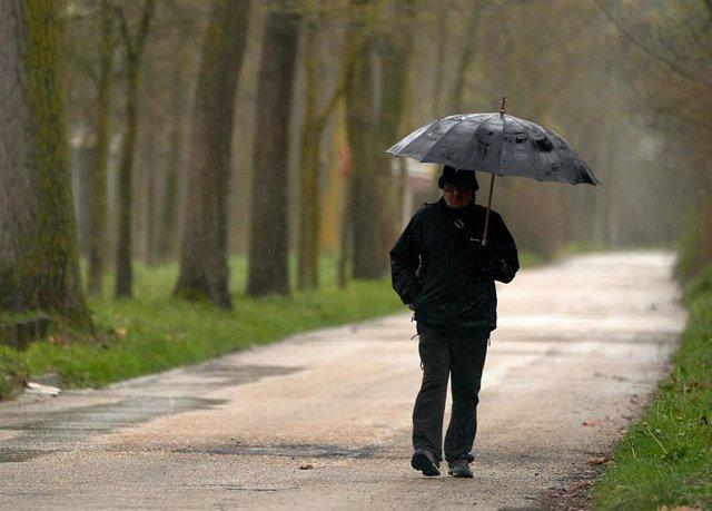 Archivo - Una persona se refugia con un paraguas de la lluvia