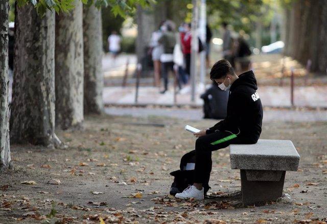 Archivo - Un alumno espera sentado antes de realizar los exámenes de la EBAU en las afueras de la Facultad de Derecho de la Universidad Complutense de Madrid (UCM)