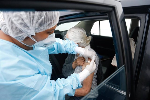 HANDOUT - 23 April 2021, Peru, Lima: An elderly woman in a car is administered a Corona vaccine. Photo: Karel Navarro/Peru's Ministry of Health/dpa - ACHTUNG: Nur zur redaktionellen Verwendung und nur mit vollständiger Nennung des vorstehenden Credits