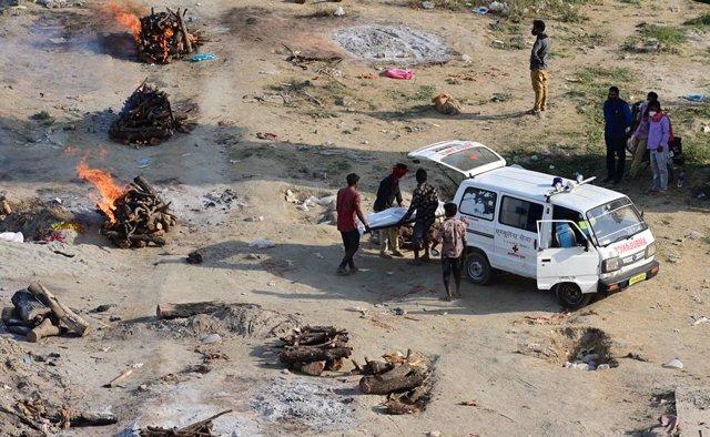 Imagen de archivo de familiares y paramédicos cremando el cuerpo de un fallecido por el coronavirus.