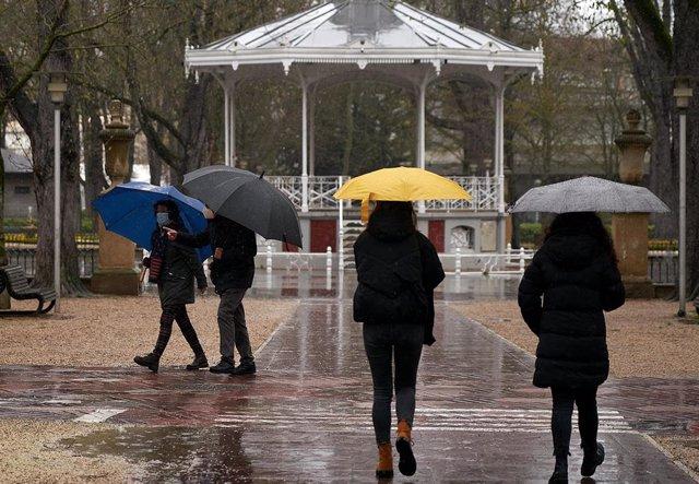 Archivo - Varias personas se refugian con un paraguas de la lluvia en Vitoria