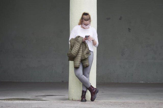 Una mujer espera con el móvil en Pamplona, Navarra (España).