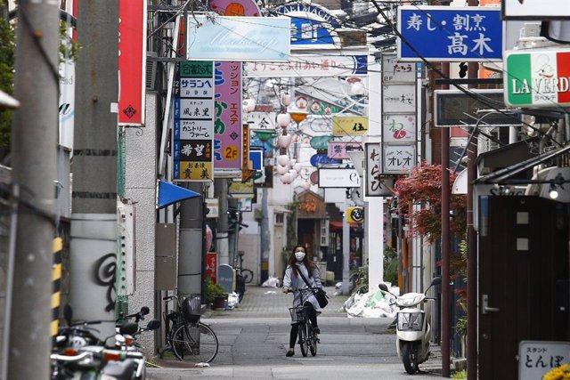 Archivo - Una mujer con mascarilla recorre en bicicleta una calle de Tokio