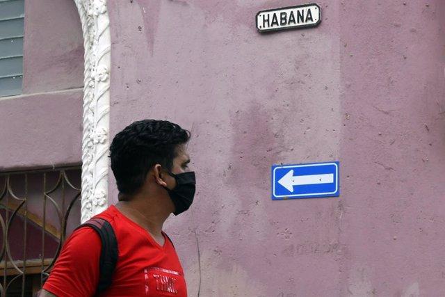 Una persona con mascarilla pasea por La Habana