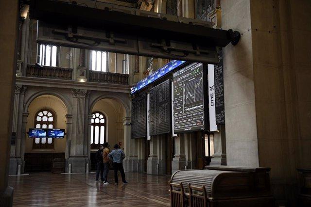 Un grupo de personas realiza una fotografía a los valores del Ibex 35 en el Palacio de la Bolsa, a 19 de abril de 2021, en Madrid, (España). Este lunes está marcado por una subida del Ibex del 0,2%, lo que ha llevado al selectivo a situarse en los 8.630,5