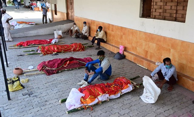 27 April 2021, India, Prayagraj: Family members wait with bodies of their relatives who died of Covid-19 to be cremated at an electric crematorium in Prayagraj. India hit record numbers of Covid-19 infections worldwide for the sixth day running on Tuesday