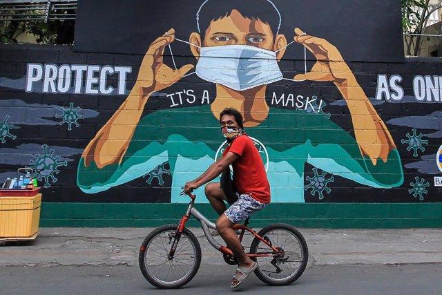Un hombre cicula en bicicleta por una calle de Manila